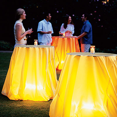 Outdoor garden party tables with yellow tablecloth with back lighting under the table