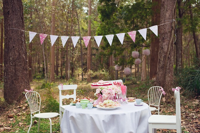 Outdoor woodland picnic with white round table, pink accessories and pink bunting overhead