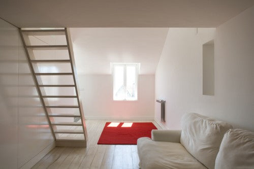 Cream living room under a mezzanine floor and a red rug