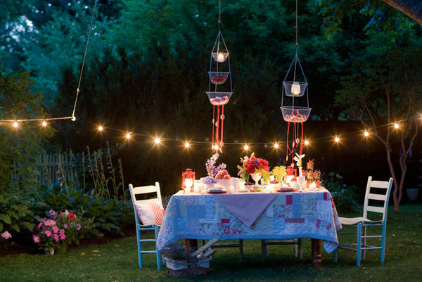 Garden party at dusk, with table setting and fairy lights hanging between trees