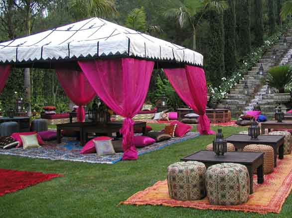 Amazing large garden gazebo, with dark pink voile canopy, stood above a large garden rug and table setting