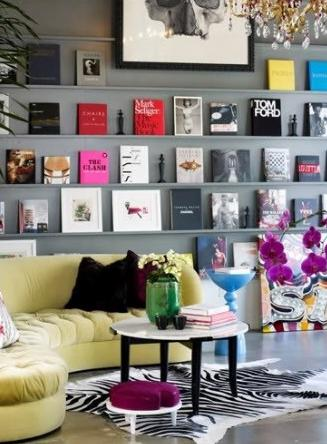 Large grey book rack with curved yellow corner sofa in front of it
