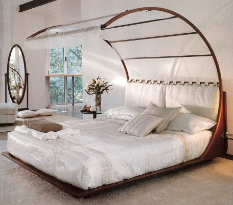 A fresh white bedroom with a bed that has a curved canopy over the bed, covered in white voiles