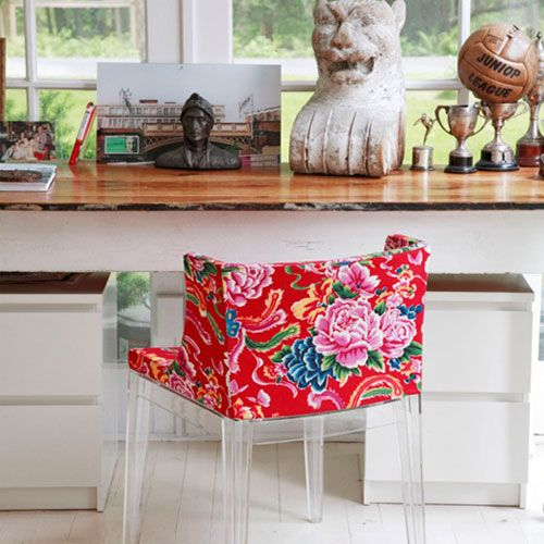 Red floral upholstered transparent leg chair next to a wooden writing desk