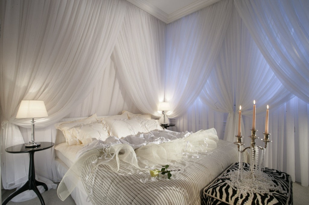Elegant white bedroom with white bedding and white voile canopies all around the bed