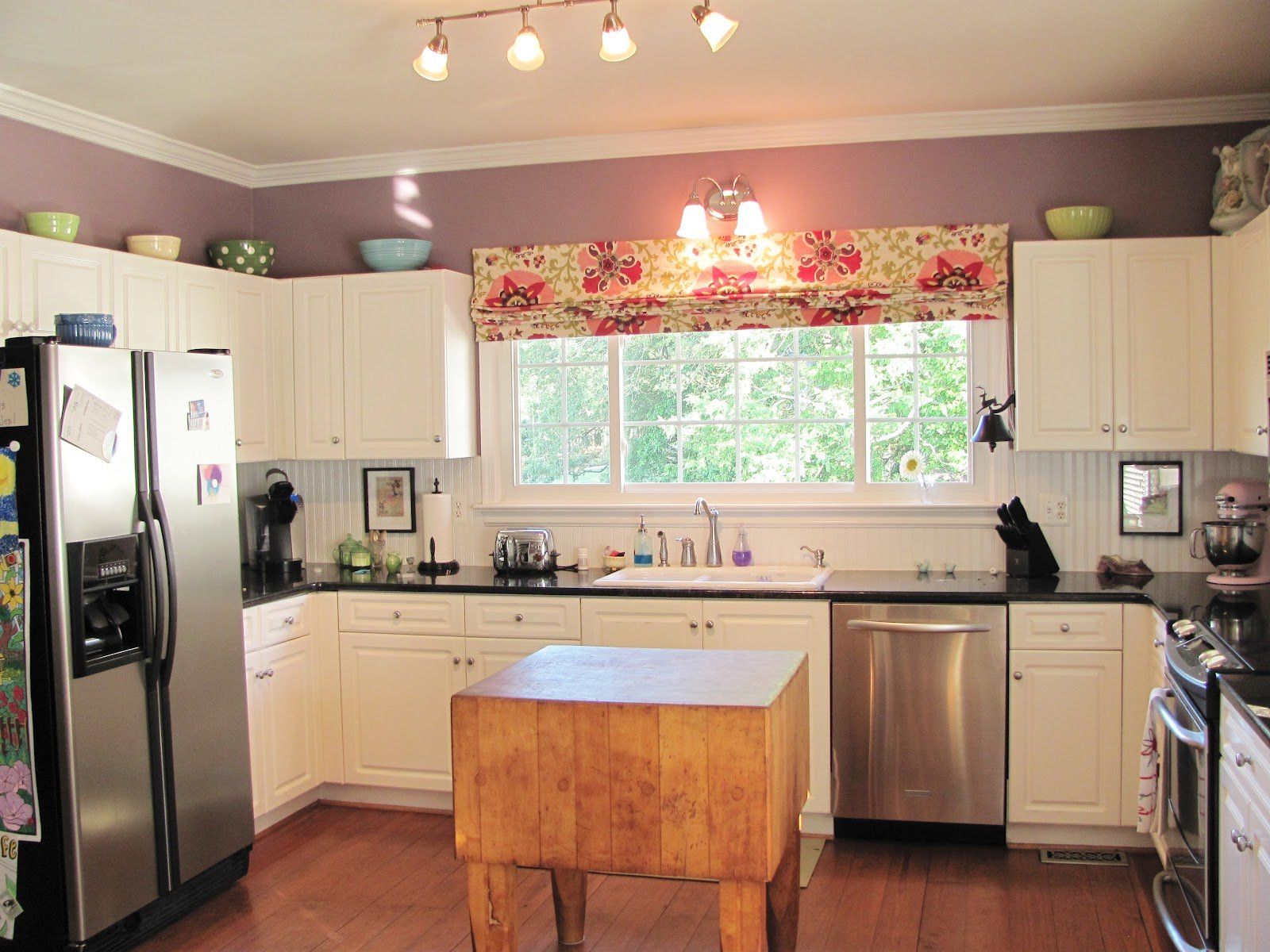 Mauve and cream kitchen with square wooden island in the middle of the room and colourful pink roman blind at the window