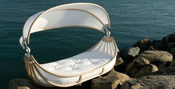 Wood frame day bed on the rocks, by the sea, looks like a Moses basket