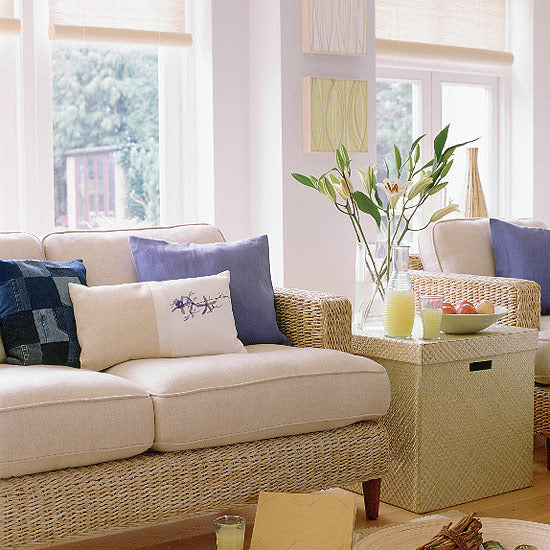 White living space, with wicker sofa and arm chairs, with cream seat pads and blue, white and beige cushions