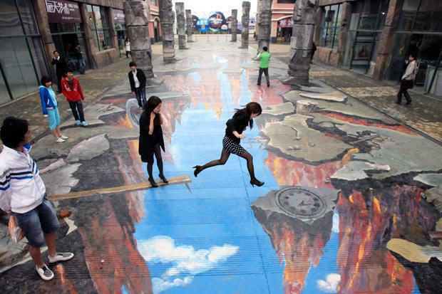 Perspective outdoor pavement artwork, that looks a earthquake ravine, with two passers by leaping over the ravine