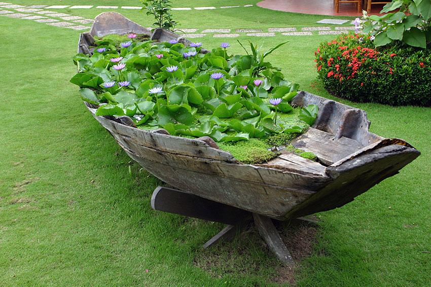 Decrepid wooden rowing boat filled transformed into a water feature with waterlilies on the top