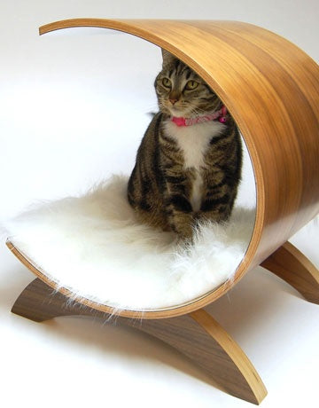 Wooden c-shaped cat bed on a wooden stand with white fluffy rug for comfort