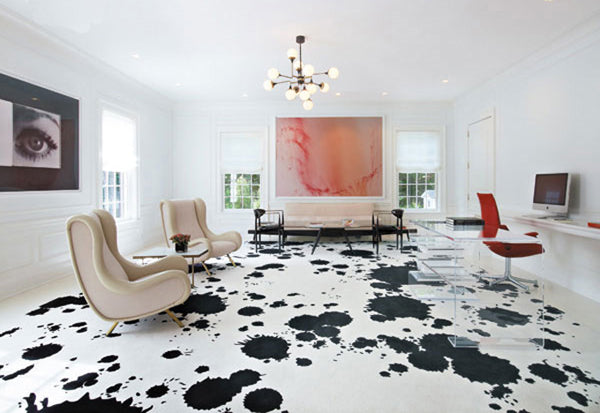 White living space and home office with white and black flooring, that resembles cow skin