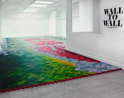 Herringbone style flooring that fades from dark green to yellow, then blue and red and burgundy in a room with white walls