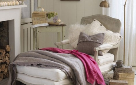Cream living room with arm chair and footstool draped in grey and pink throws