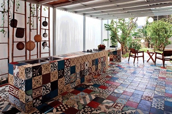 A kitchen that extends out into the garden, with lots of patterned floor tiles covering the kitchen units and all over the floor
