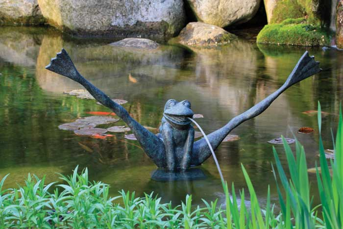 A water feature with a statue of a frog doing the splits, with water coming out of his mouth