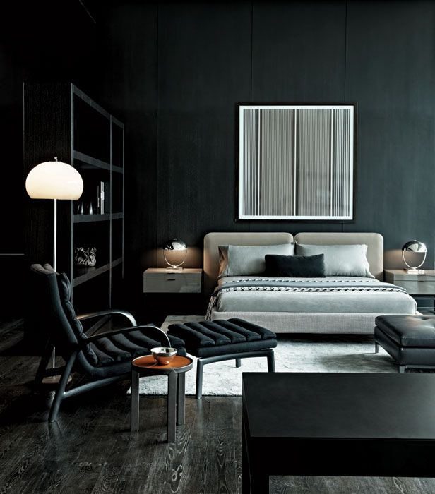 Black bedroom with black chair, shelves and desk and grey bed and bedding