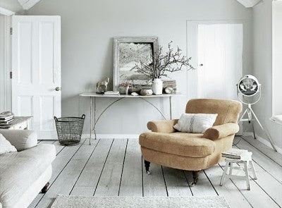 White and light green living room with grey floor boards and beige armchair