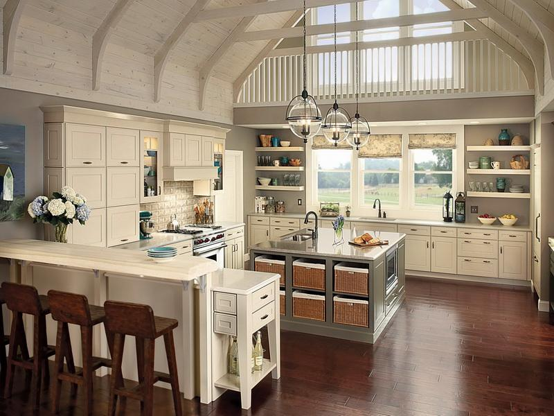 Amazing and large country farmhouse kitchen in cream and beige with dark wooden floors, and grey kitchen island