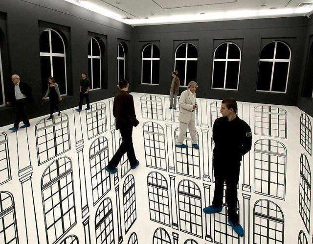 Indoor perspective wall and floor art that makes it appear like people are floating next to buildings