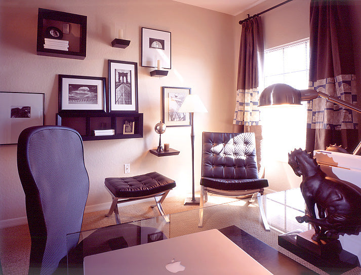 A cream and soft purple home office with photographs framed on the walls and a glass computer desk