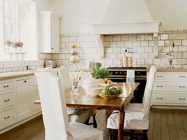 Fresh modern country kitchen with white ceramic wall tiles, natural wooden flooring and dining table