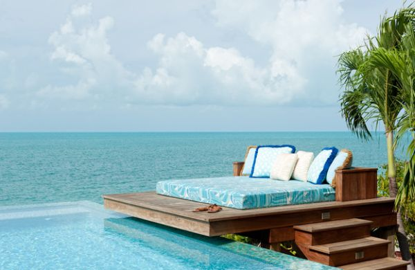 Day bed on wooden decking next to an infinity pool, overlooking the sea