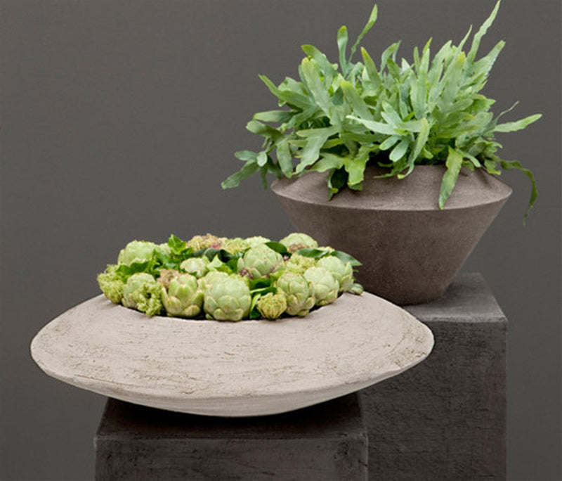 Stone and ceramic planters on two stone plinths, with greenery in each