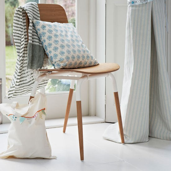 Natural wood finish chair with white metal sections, with cushion on top