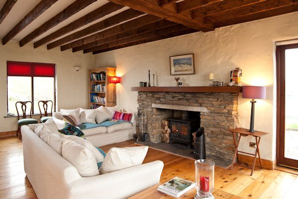 White walled cottage with stone fireplace and dark wood exposed ceiling beams