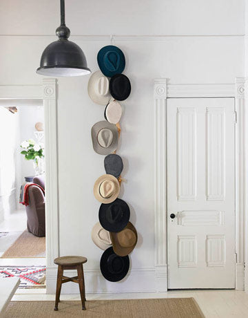 A number of different hats hung on a rope in a white room