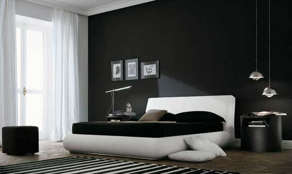 Black and white bedroom with black bed side table, black bedding, black walls and white bed frame
