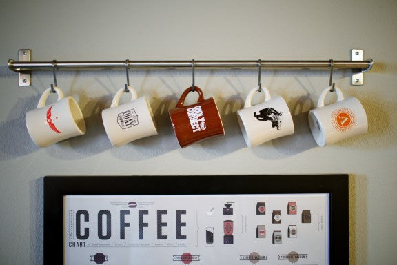 Coffee mugs hung from a metal rail in the kitchen
