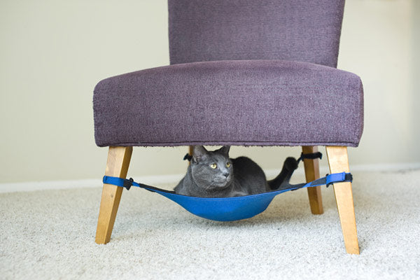 Light purple armchair with a blue hammock underneath as a cat bed