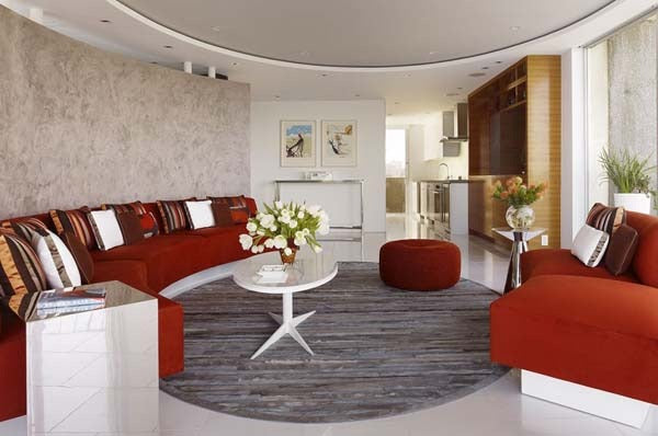 Living room with a curved design, cream walls and red curving sofa