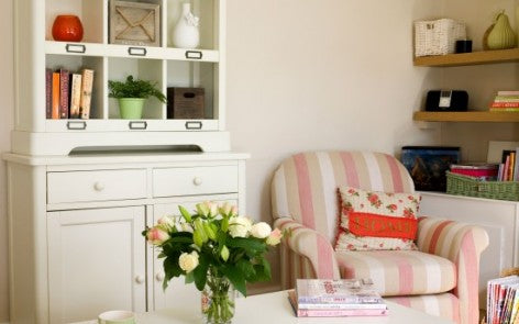 Cream living room with cream unit and cream, beige and pink striped arm chair