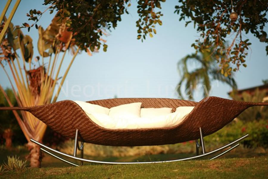 A metal frame day bed with woven base and cream cushions