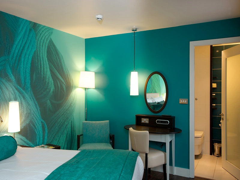 An aqua green bedroom with aqua walls, bed runner and pillows, then white bedding