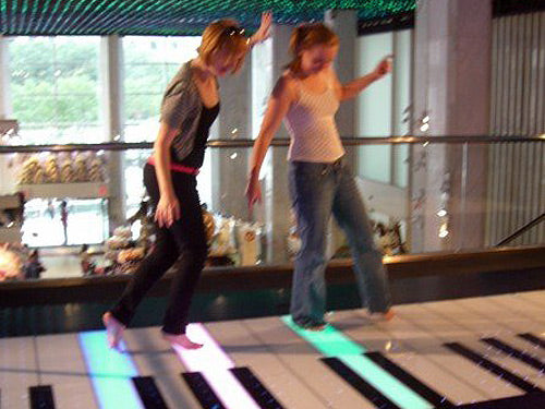 Two woman dancing on a large floor piano, like from the film Big