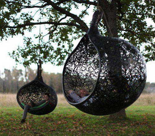 Black pod day beds suspended from trees