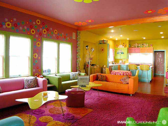A very brightly coloured large living room in orange, pink, green and yellow