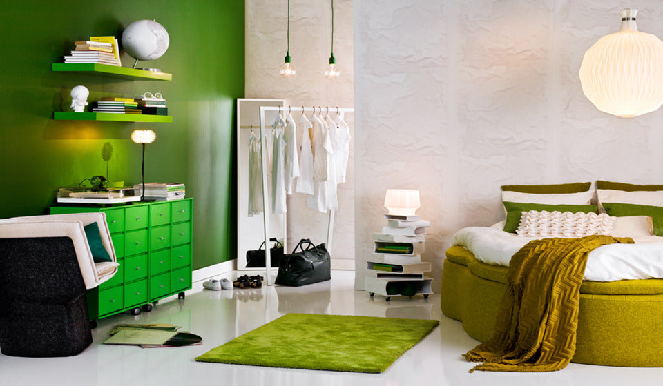 White and green bedroom with one green wall and one white wall, green shelves drawers, rug and olive green bed base