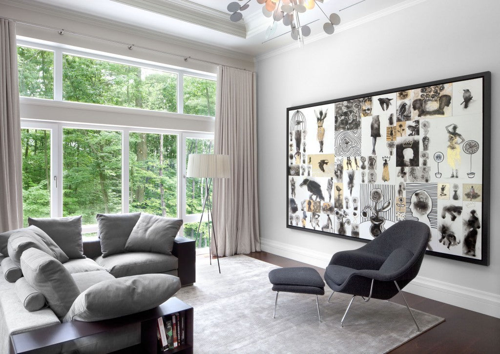 Light grey and cream living space, with grey sofa and large windows looking out on to a wood