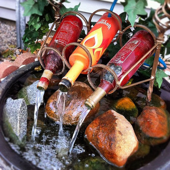 Small garden water feature with bottles of wine pouring water into a small rock pool