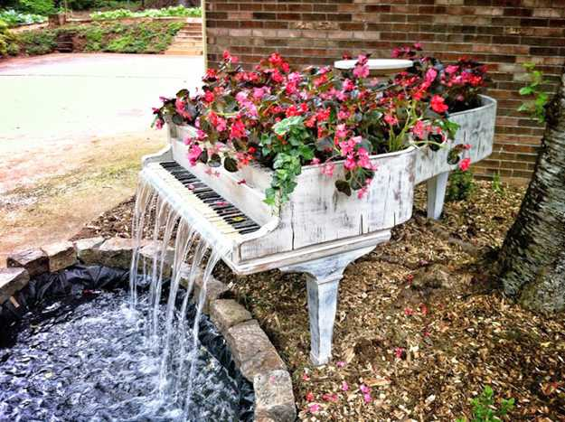 White distressed looking piano transformed into a planter for pink flowers, with water falling over the keys and into a pond
