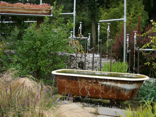 Rusting metal bathtub as a water feature in a garden with lots of pipes and taps overhead dripping into the tub