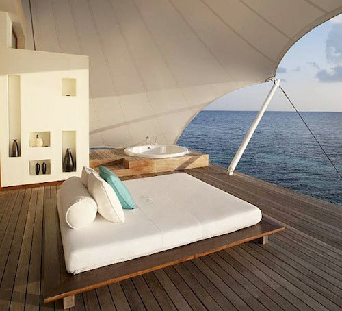 Wooden decking by the sea, with white daybed and white canopy