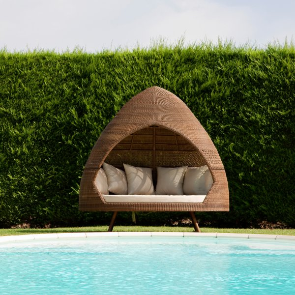 Wigwam style wicker daybed next to a swimming pool