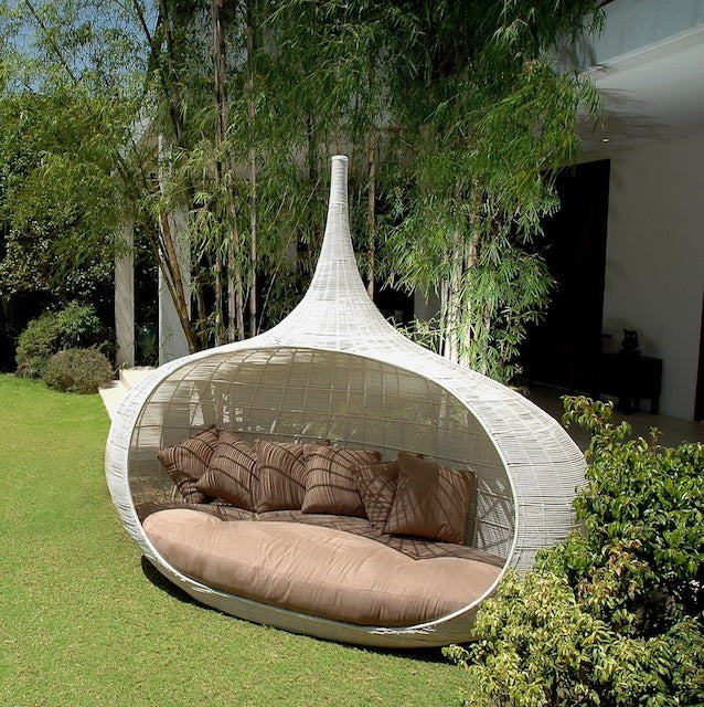White pod day bed in a green garden
