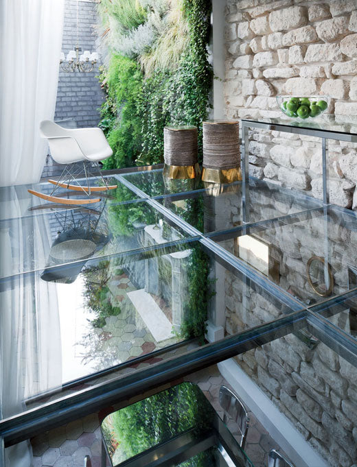 Outdoor mezzanine glass floor, above a dining room, with modern white rocking chair by the edge of the floor